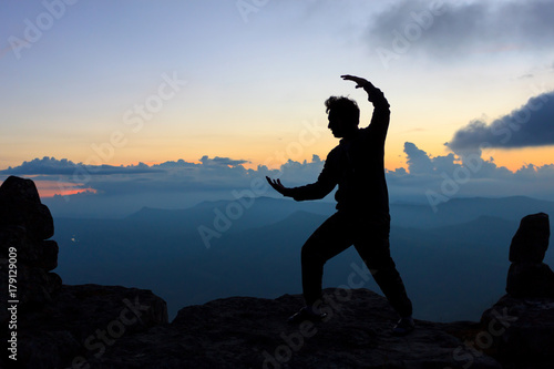 Tai Chi practising on the peak of mountain during sunset , silhouette