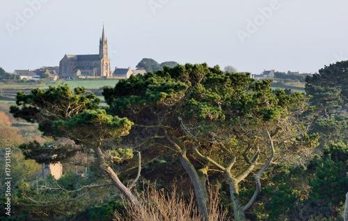 La pose en embrasure Kaki L'église de Plougrescant en Bretagne vue depuis les hauts rochers de Pors-Scaff