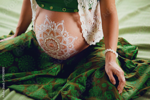 Papiers peints Style Boho White mehendi on big pregnant belly. Expectation of baby in boho lifestyle.