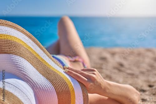 Obraz na dibondzie (fotoboard) Młoda kobieta w kapeluszu maski o odpoczynek na wybrzeżu.
