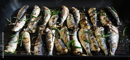Fotografía  Sardines in a frying pan grilled with spices and rosemary.