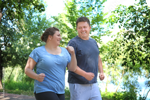 Photo Overweight couple running in green park