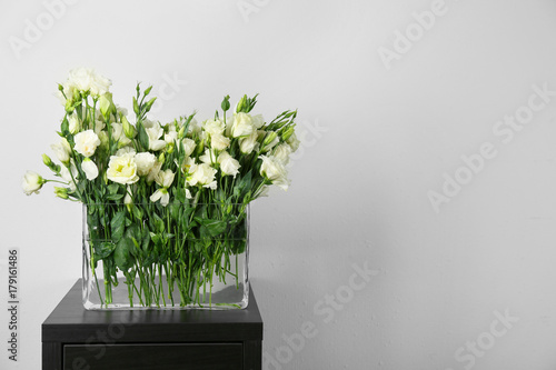 Foto op Canvas In het ijs Vase with beautiful eustoma flowers on table against light wall