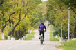 girl with a backpack on her back riding a bicycle