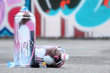 Fototapeta Młodzieżowe - Several used spray cans with pink and white paint and caps for spraying paint under pressure is lies on the asphalt near the painted wall in colored graffiti drawings