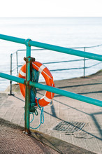 Lifebuoy On A Harbour Fence By The Sea