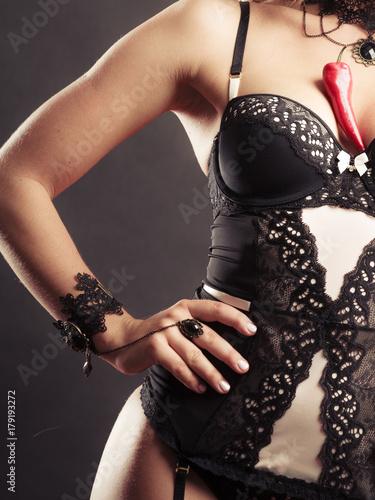 Fototapeta Woman wearing sexy lingerie holding chilli on chest obraz na płótnie