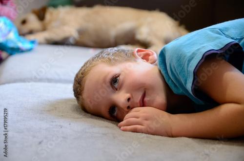 Fototapeta Jack Russell terrier leży na kanapie z chłopczykiem obraz