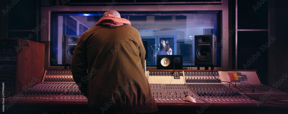 Fototapeta Musicians producing music in professional recording studio