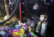 A Boy And His Father Try Their Hand At A Claw Crane Game At An Arcade