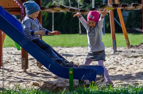Rodzeństwo dzieci bawi się na planu zabaw w jesienny słoneczny dzień.