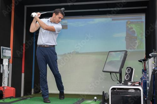 Fotografía  Man practicing golf swing using simulator