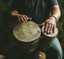A Man Playing A Set Of Bongos