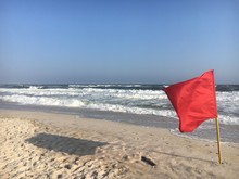 A Red Flag On The Beach At Rob...