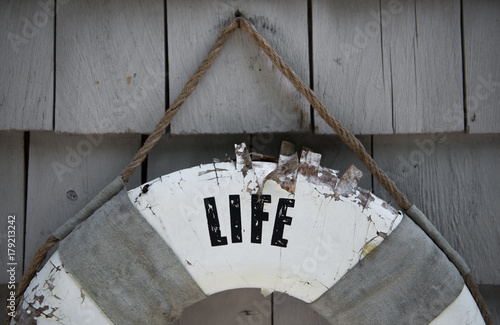 Old life preserver hangs on a shingled exterior wall