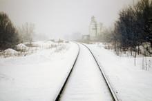 Train Tracks And Grain Silos In Snow