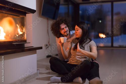 Ingelijste posters Dance School happy multiethnic couple sitting in front of fireplace
