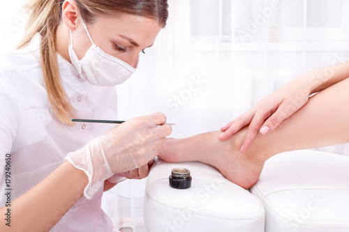 Beautician does pedicure at the beauty salon. It deals with a thin brush on the nails of gold sequins. The concept of beauty and health