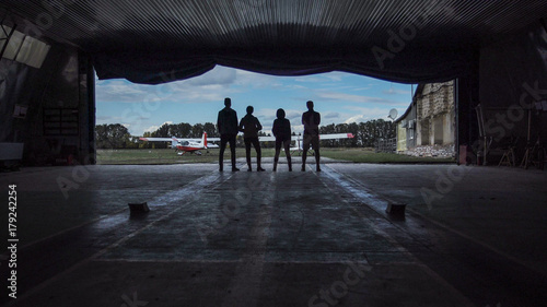 Fototapeta Four people standing in an aircraft hangar silhouetted against the sky watching two small aircraft outside in a low angle view obraz