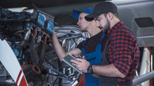 Two Flight Mechanics Doing A Pre Flight Check Or Maintenance On A Small Single Engine Aircraft Using Digital Tablet In A Hangar In A Close Up View Of Them Working On The Engine.