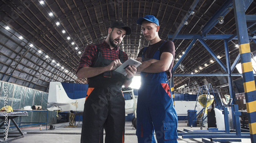 Two flight engineers walking through a large aircraft hangar talking and gesturing together