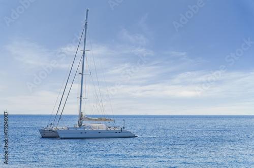 Plakat Duży biały luksusowy jacht zadokowany na morzu, ale gotowy do podróży w dowolnym momencie do tropikalnej pięknej wody
