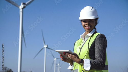 Female engineer wearing hard hat standing with digital tablet against wind turbine on sunny day and looking at camera smilingly