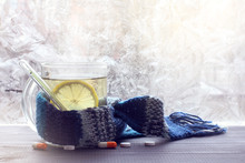 Treatment Of Colds In Winter/ Hot Infusion With Lemon In Mug, Wrapped In A Scarf With A Thermometer On The Background Of Pills And Frozen Windows