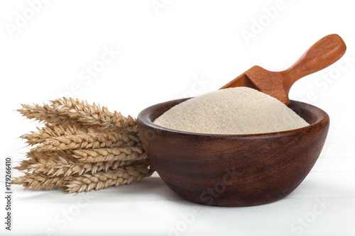 wheat semolina in a wooden bowl on a white table