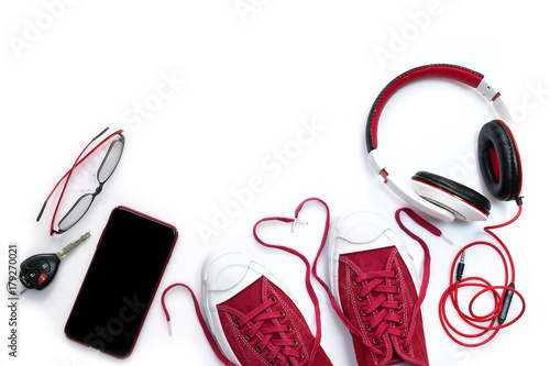 Sneaker shoes , mobile phone and other accessories such as headphone , car key and eyeglass on white background , top view and copy space