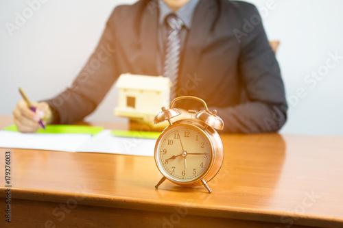 Fotodibond 3D selekcyjna ostrość budzik z biznesmena kontraktu podpisuje nieruchomość jego budynek mieszkalny na biurku