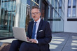 Portrait of businessman using laptop outdoors