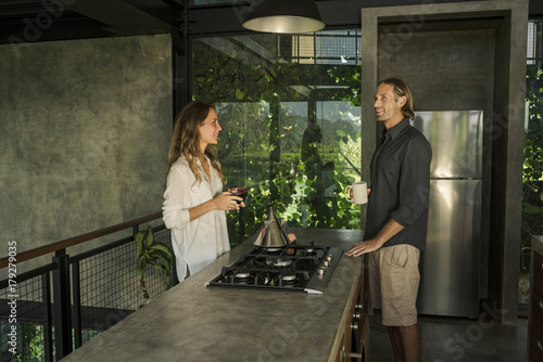 Couple having breakfast and smiling in modern design kitchen with glass facade surrounded by lush tropical garden