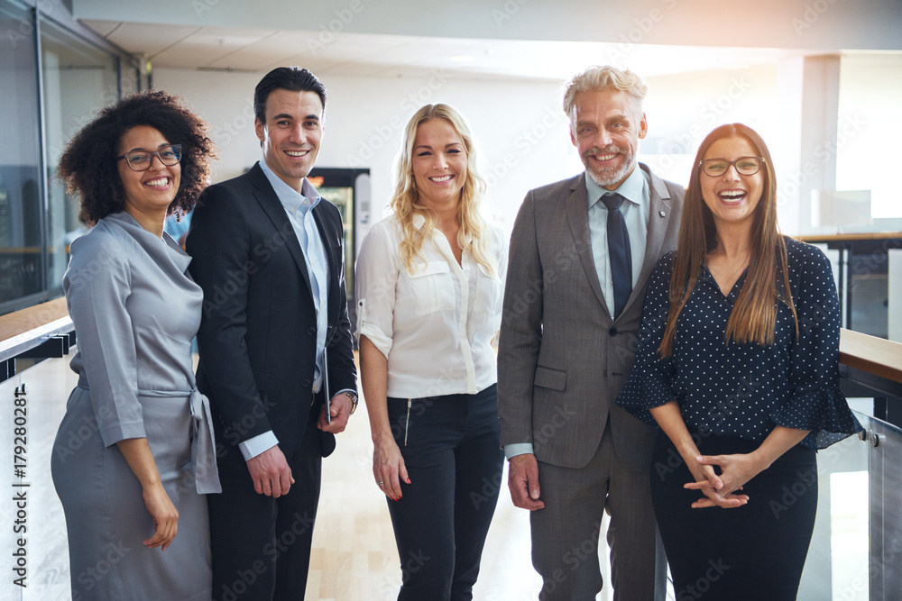 Fototapety, obrazy: Diverse group of smiling colleagues standing together in an office
