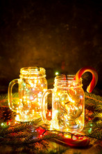Christmas Card With Glowing Lights And Candy Cane In Glass Jars On Dark Background.