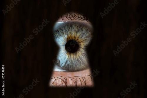 Photo  Female blue eye looking through the keyhole