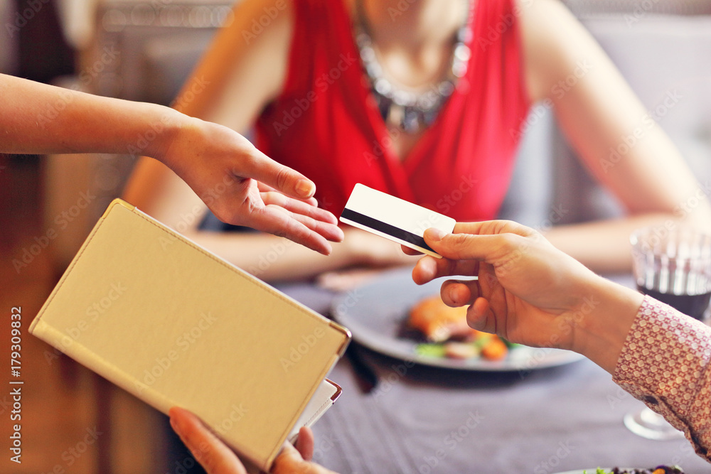Fototapeta People paying in restaurant by credit card reader