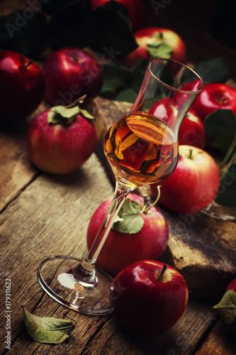 Strong golden alcoholic drink from apples, vintage wooden background, selective focus