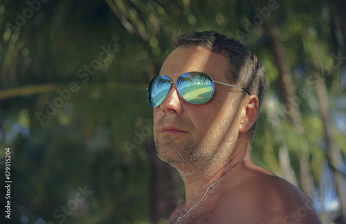 Serious man wearing sunglasses in summer