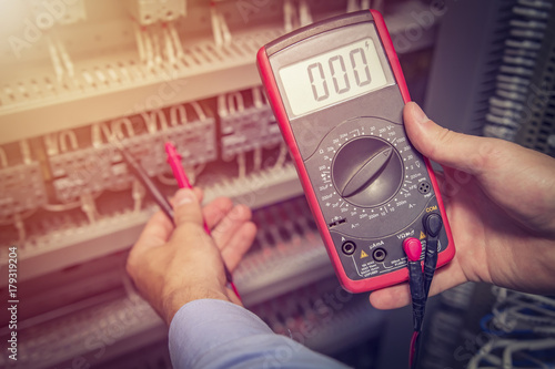 Pinturas sobre lienzo  Service engineer with multimeter tester in hands close up