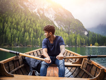 Young Casual Man Sitting In Boat And Rowing While Looking Away On Background Of Lake And Mountains.