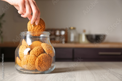 Canvastavla Woman taking oatmeal cookie from glass jar