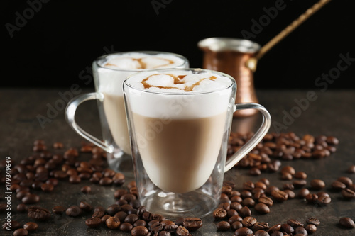 Fotobehang Koffiebonen Glass cups with latte macchiato on table against black background