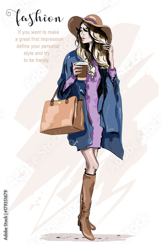 Beautiful young woman in hat. Stylish woman in fashion clothes. Fashion lady. Autumn outfit. Hand drawn girl holding coffee cup. Sketch. Wall mural