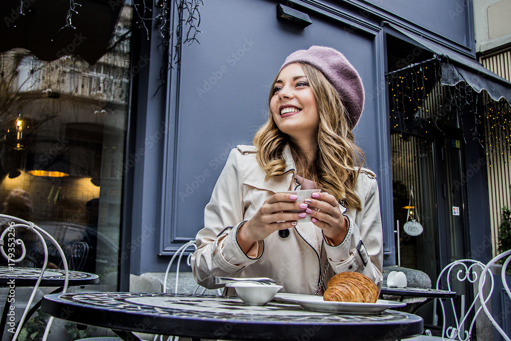 Fototapety, obrazy: Cheerful french woman. Low-angle view of beautiful blonde woman in beret looking away and smiling while sitting in french vintage cafe. Woman drinking coffee with croissant. French breakfast concept.