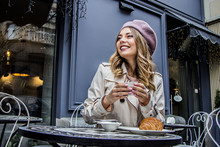 Cheerful French Woman. Low-angle View Of Beautiful Blonde Woman In Beret Looking Away And Smiling While Sitting In French Vintage Cafe. Woman Drinking Coffee With Croissant. French Breakfast Concept.