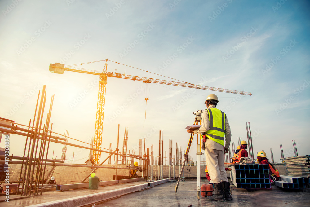 Fototapety, obrazy: Surveyor builder Engineer with theodolite transit equipment at construction site outdoors during surveying work