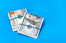 Two Packs Of Folded Dollar Bills With Rubber Band On A Blue Background.