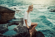 Young Woman Sitting On Rocks At The Ocean
