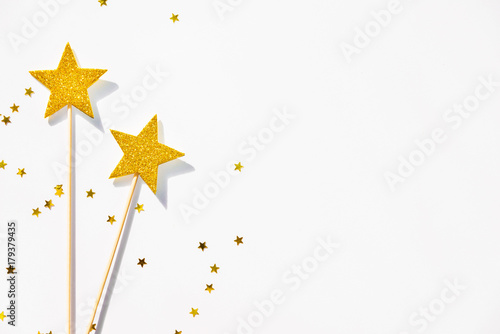 Fotografie, Obraz  Two golden party magic wands and sequins on a white background